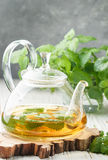 Herbal tea in a transparent teapot on the table and sprigs of fresh Melissa lemon balm and mint Stock Photo