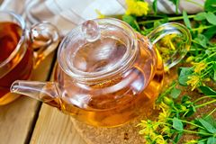 Herbal tea from tutsan in glass teapot with cup Royalty Free Stock Images