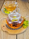 Herbal tea from tutsan in glass teapot on stand Royalty Free Stock Photos