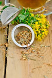 Herbal tea from tutsan in strainer with cup on board Royalty Free Stock Image