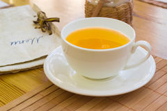 Herbal tea in the white cup on a saucer Stock Photos