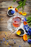 Herbal tea with wild flowers(calendula, blue cornflower) on wood Stock Photography