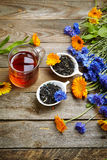 Herbal tea with wild flowers(calendula, blue cornflower) on wood Royalty Free Stock Images