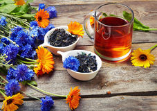 Herbal tea with wild flowers(calendula, blue cornflower) on wood Stock Images