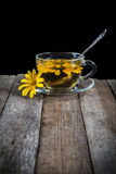 Herbal tea with yellow daisy on wooden table Stock Photo