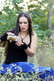 Herbalist. Young girl collects medicinal herbs in the forest Stock Photography