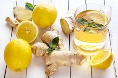 Herbata, cytryna, imbir, mennica na białych deskach Zdjęcie Royalty Free