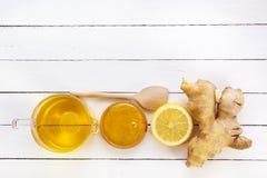 Herbata, cytryna, imbir, miód i mennica na białych deskach, na widok Fotografia Royalty Free