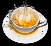 Herbata nalewa w spodeczek z pluśnięciami na czarnym tle fotografia stock