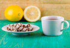 Herbata w filiżance i opłatków tubules w talerzu dalej zdjęcie stock