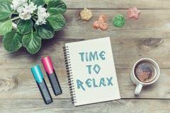 Herbata z cukierkami i inskrypcją w notatniku: Czas relaksować Obrazy Stock