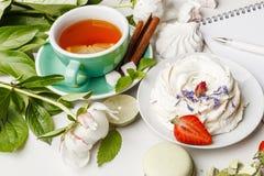 herbata z tortami, owoc i kwiatami na białym stole, zdjęcia stock