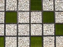 Herbe artificielle et mur en pierre comme fond Image stock