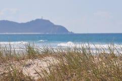 Herbe de bord de la mer avec la vague déferlante et le phare Photo libre de droits