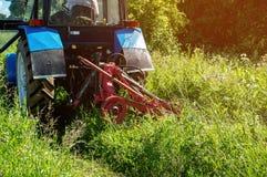 Herbe de fauchage verte de tracteur de ferme haute dans un jour d'été ensoleillé Plan rapproché Photographie stock libre de droits