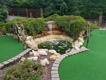 Herbe et roches artificielles vertes sur le terrain de golf miniature photo stock