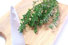 Herbe organique de thym sur le hachoir avec le couteau Photos stock