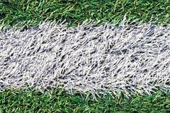 Herbe verte artificielle avec la rayure blanche du terrain de football Images stock
