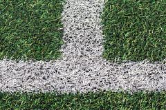 Herbe verte artificielle avec la rayure blanche du terrain de football Photographie stock