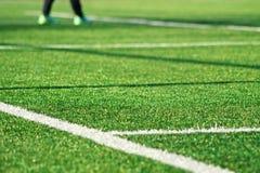 Herbe verte artificielle avec la rayure blanche du terrain de football Image libre de droits