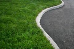 Herbe verte et asphalte noir Image libre de droits