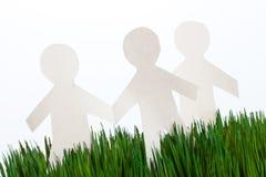Herbe verte et hommes à chaînes de papier Images stock