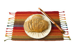 Herbed Bread with Bread Saw. Sliced wheat herb bread on a multicolored mat with an Appalachian bread saw stock photo