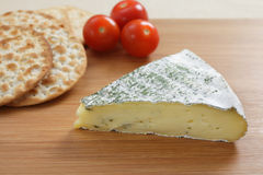 Herbed brie and crackers. A cheeseboard with a herbed French brie, crackers and tomatoes Stock Photography