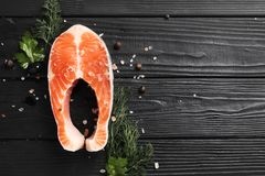Herbes de poivre et de sel de bifteck saumoné sur la table noire image stock