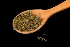 Herbes de Provenza (miscela delle erbe secche) in cucchiaio di legno su fondo nero Immagini Stock