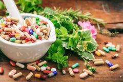 Herbes et pilules dans un mortier sur le fond en bois photographie stock