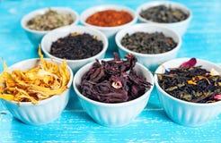 Herbes et thés dans des cuvettes pour faire le thé sur le Cl bleu de fond de table Image stock