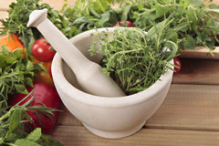 Herbes fraîches avec un mortier et un pilon et des légumes Images stock