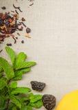 Herbes pour le thé et un citron sur un fond de toile Photographie stock libre de droits