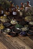 Natural and alternative medicine.  Place for logo and text. Herbs in bowls, mortar and medicine bottles on wooden rustic table Royalty Free Stock Image