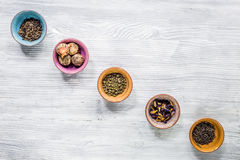 Herbs in colorful bowls to make tea on light table background top view mock-up Stock Photo