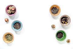 Herbs in colorful bowls to make tea on white table background top view mock-up Royalty Free Stock Image