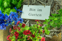 Herbs, flowers and green leaves with a sign in the garden. In German stock photo