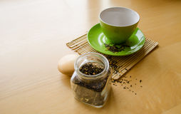 Herbs in glass jar and spilled tea near cup on wooden tray Royalty Free Stock Photos
