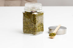 Herbs are in the glass jars with spoons. Stock Image