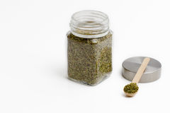 Herbs are in the glass jars with spoons. Stock Photography