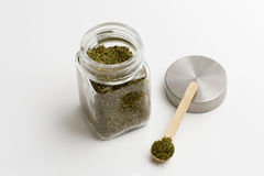 Herbs are in the glass jars with spoons. Stock Photo