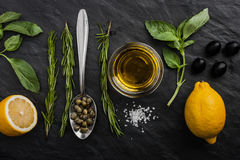 Herbs mix with  lemons , capers and olives on the black stone table Stock Images