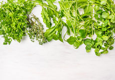 Herbs mix for salad and courses on white wooden background. With place for text Stock Photos