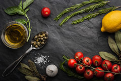 Herbs mix with tomatoes, lemon and olive oil on the black stone table. Green basil ,rosemary and bay leaf with salt , tomatoes , lemon ,capers, garlic and olive stock image