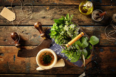 Herbs, oil and mezzaluna over old wooden table Stock Photos