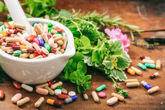 Herbs and pills in a mortar on wooden background Stock Photography