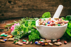 Herbs and pills in a mortar on wooden background Stock Photo