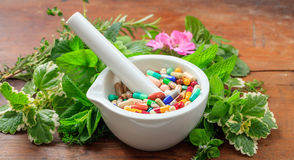 Herbs and pills in a mortar on wooden background Royalty Free Stock Photography