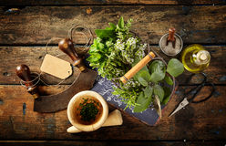Herbs, scissors and mezzaluna over rustic table Royalty Free Stock Photography